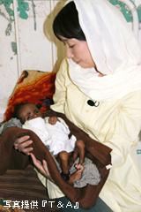 病院で栄養失調の子どもを抱くアグネスさん