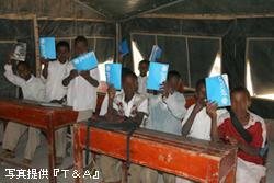 ユニセフが配布した教科書を見せる子どもたち