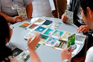 アートカードの「にたものつながりゲーム」を体験する指導者研修の受講者達。手持ちのカードの中から場札と色や形などのつながりがあるものを見つけて、皆の納得が得られるように説明することで、作品の特徴を捉え、分類する力が身につく