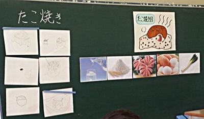 児童の描いた6個のたこ焼き(黒板左)、藤本先生の描いた「たこ焼き図」黒板右上