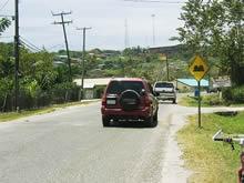 「歩行者横断、車両一旦停止」の道路標識。 車道が盛り上がっているため、車は一旦停止して 渡らざるをえない。守らないドライバーはいない。