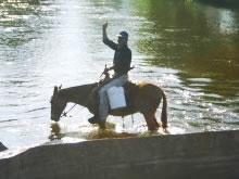 川を渡るおじさん。 馬は大切な交通手段のひとつ。